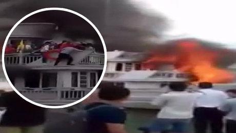 Alevler içindeki tekneden denize atlayarak kurtuldular