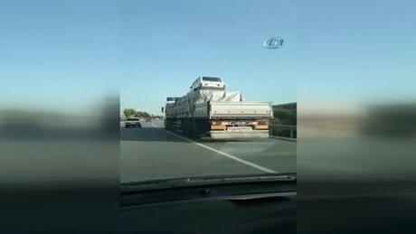 Yük dolu TIR'ın üzerinde arabayı böyle taşıdı