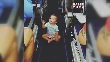 Uçaktakileri selamlamaktan mutlu olan sevimli bebek