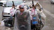 Suriyeli çocuk yağmurda karton toplayabilmek için poşetlerden kıyafet yaptı