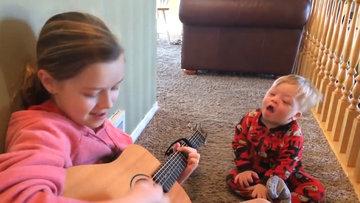 Lydia, 2 yaşındaki down sendromlu kardeşi Bo'ya gitar çalıp şarkı söylüyor