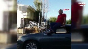 Otomobilin tavanına oturup, direksiyonu ayaklarıyla kontrol edip araç kullandı